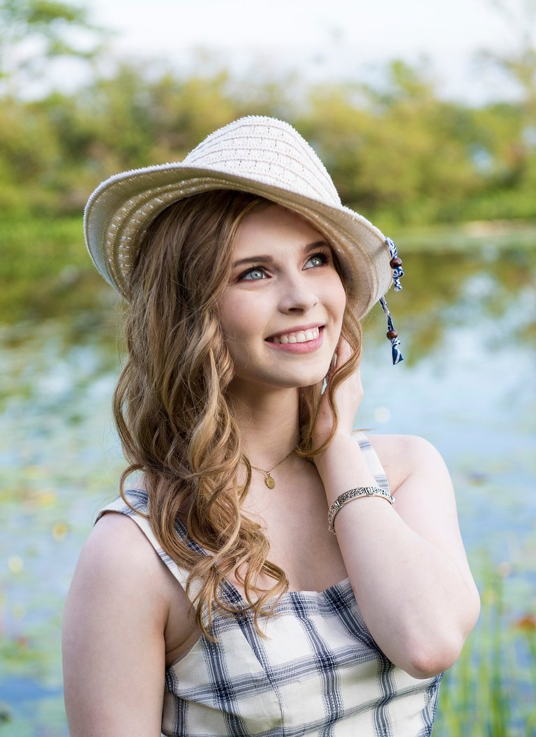 fresh faced girl with long blonde hair and hat smiles by water in Waterford park