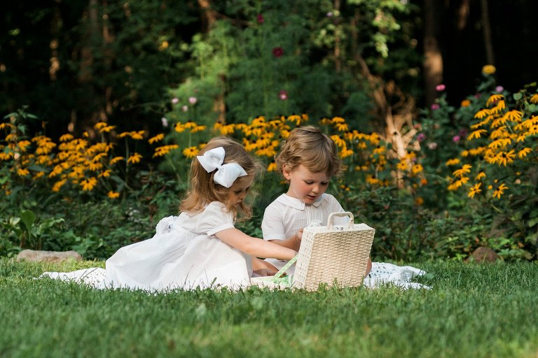 twin children have tea party in garden for photo session wearing white outfits