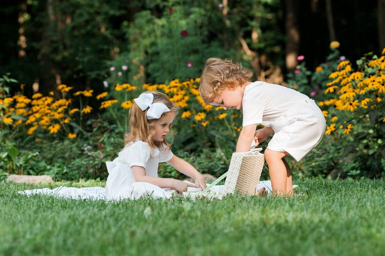 little boy and girl having a tea party in flower garden