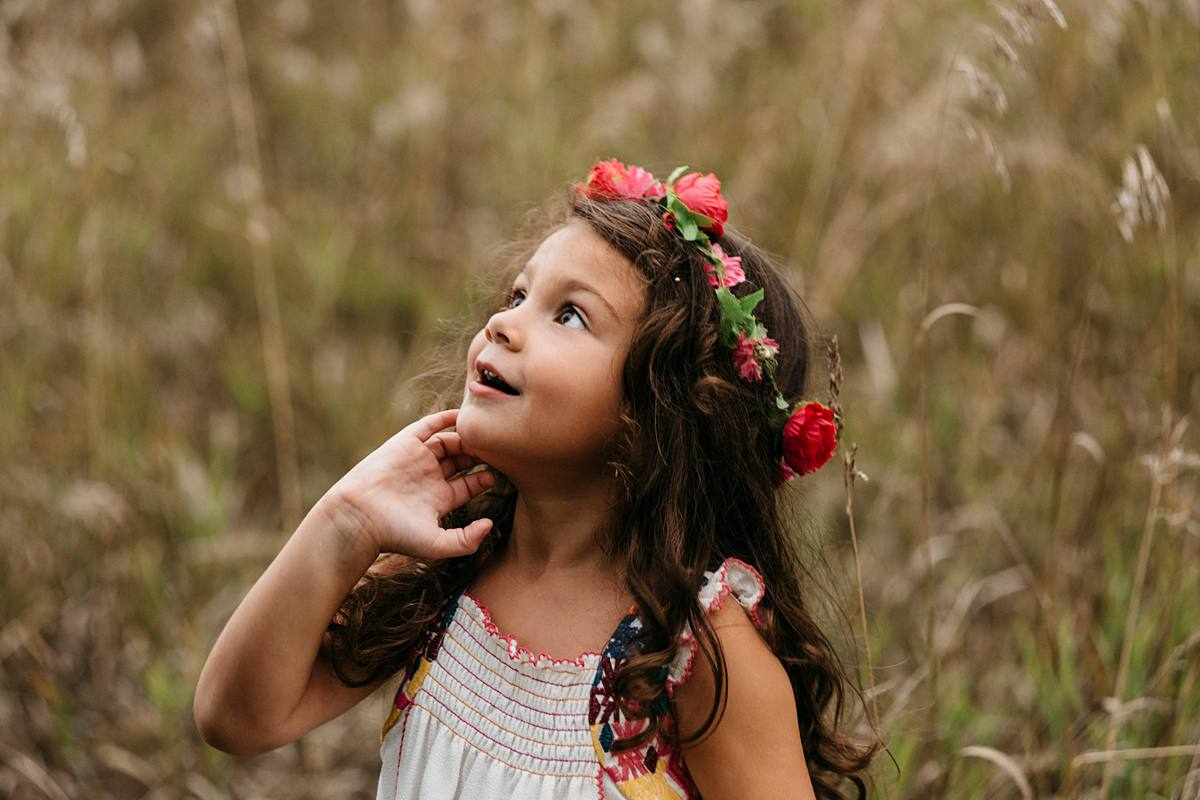 lifestyle family photo of girl wearing flower wreath