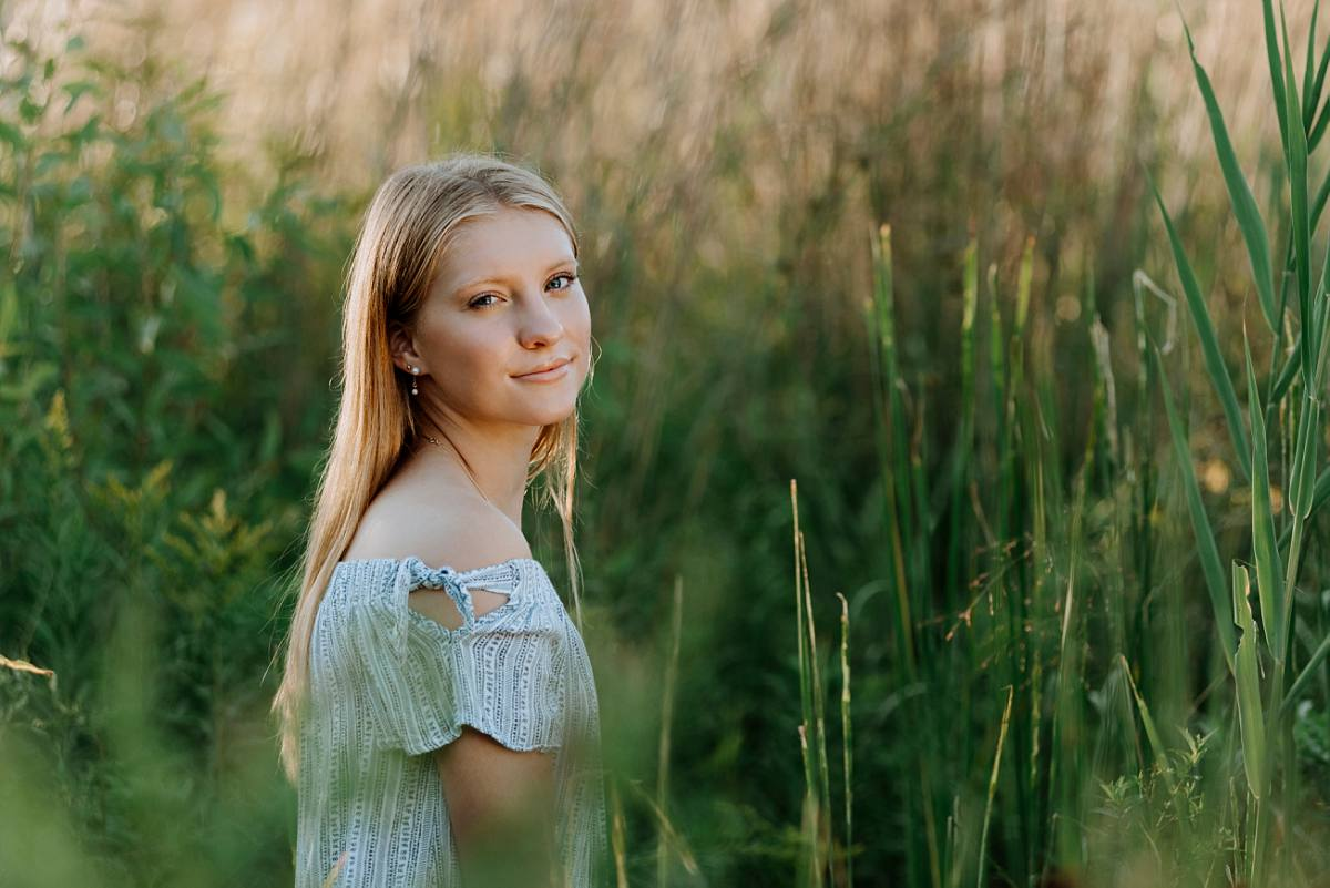 pretty senior girl posing in tall grass nature area in Waterford