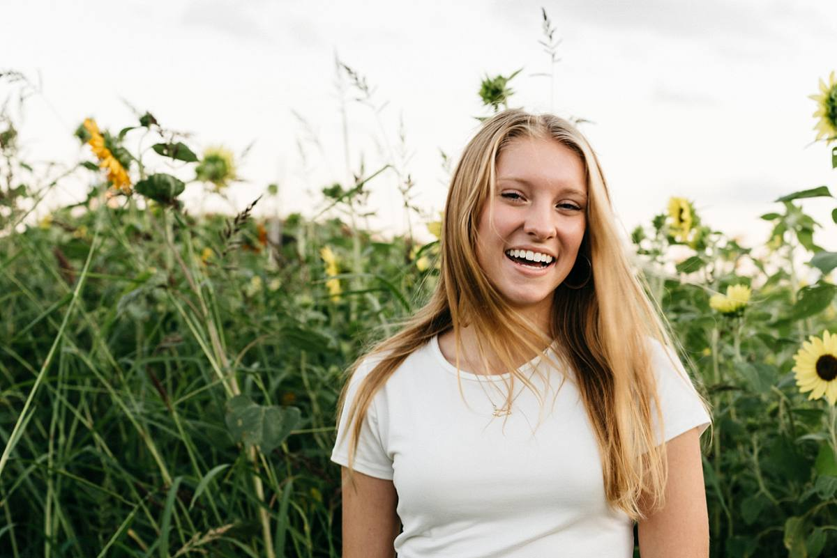 girl laughing in fun senior pictures near fields and parks in Waterford