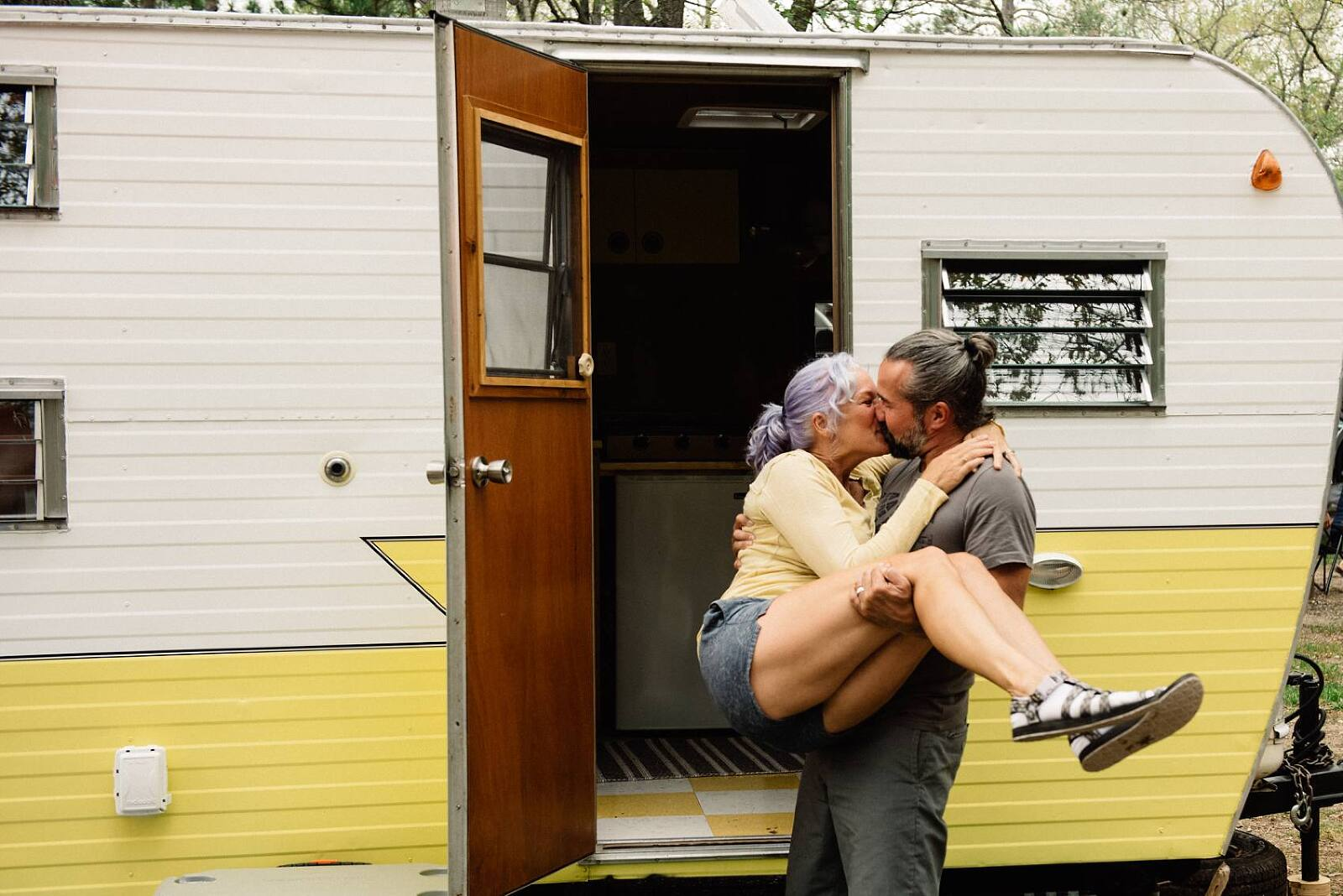 photographer couple in front of yellow layton camper