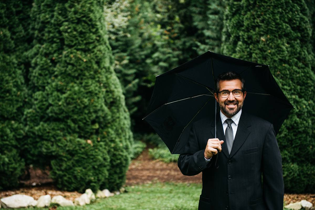 david trumbo owner in black suit under umbrella in pines